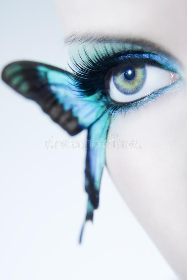 Beautiful woman eye close up with butterfly wings. And blue make up royalty free stock image