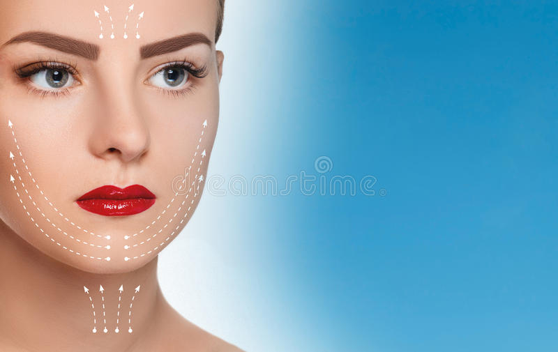 The beautiful woman face with arrows close up over blue background. The beautiful woman face with arrows close up over a blue background royalty free stock image