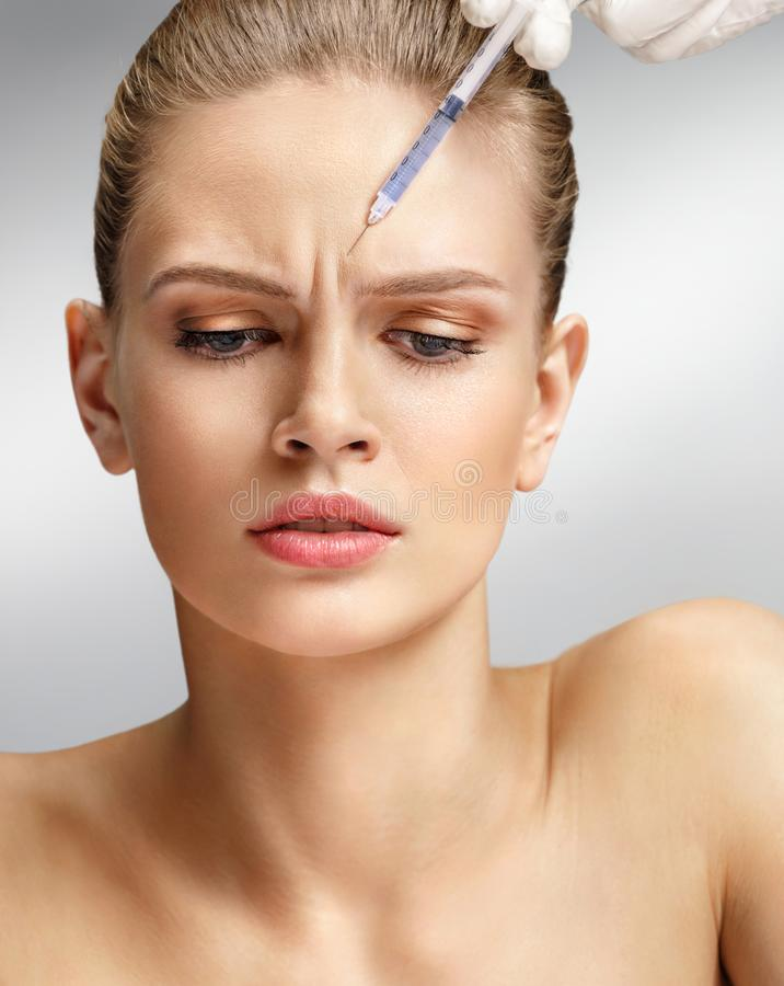 Beautiful woman face and beautician hands with syringe makes cosmetic injection in forehead. royalty free stock photography