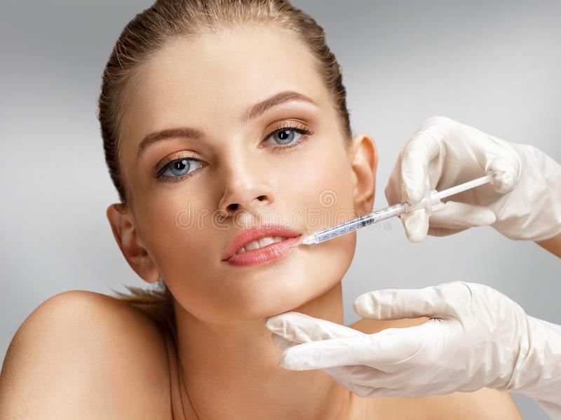 Beautiful woman face and beautician hands with syringe makes cosmetic injection in the upper lip. Clean Beauty concept stock image