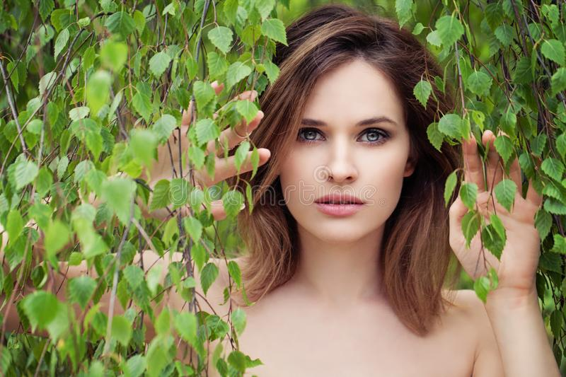 Beautiful woman face on birch leaves background. Natural beauty stock images