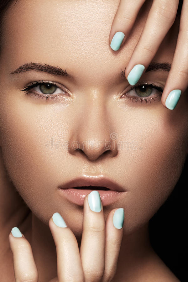 Beautiful woman face with blue nails manicure, clean skin. Make-up & cosmetics, manicure. Close-up portrait of beautiful woman model face with clean skin on stock photo