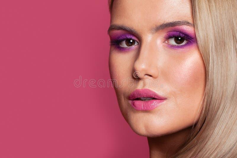 Beautiful woman face close up. Blonde hair, pink eyeshadow makeup.  royalty free stock photos