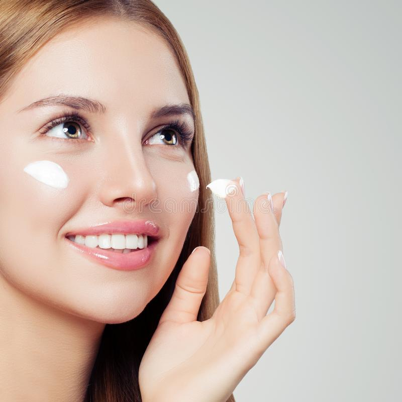 Beautiful woman face closeup. Perfect girl with healthy skin applying moisturizing cream. Skin care, beauty and facial treatment stock image