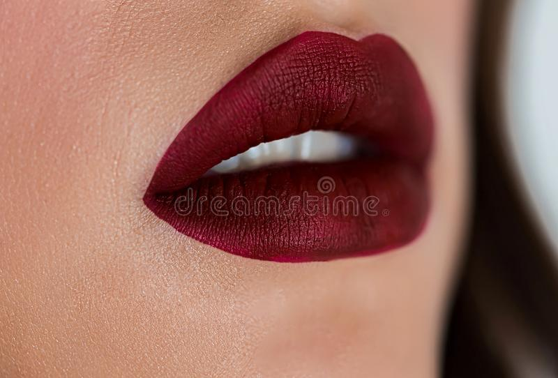Beautiful woman face with dark red lipstick, plump full lips. Closeup of girls mouth with professional lip makeup stock image