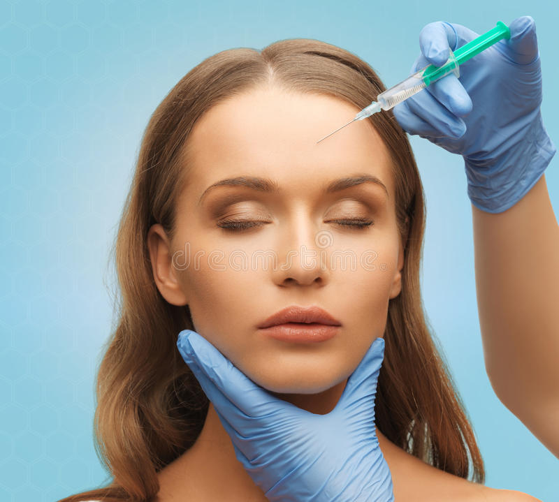 Beautiful woman face and hands with syringe. Medicine, plastic surgery, beauty, health and people concept - hands in medical glove with syringe making injection stock image