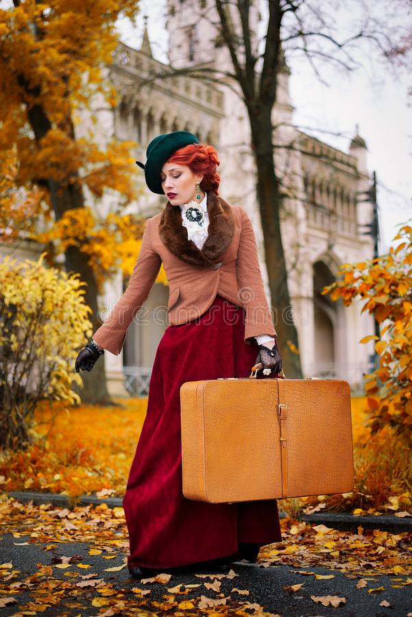 Beautiful woman face in the hat and red hair with luggage autumn travel stock photos