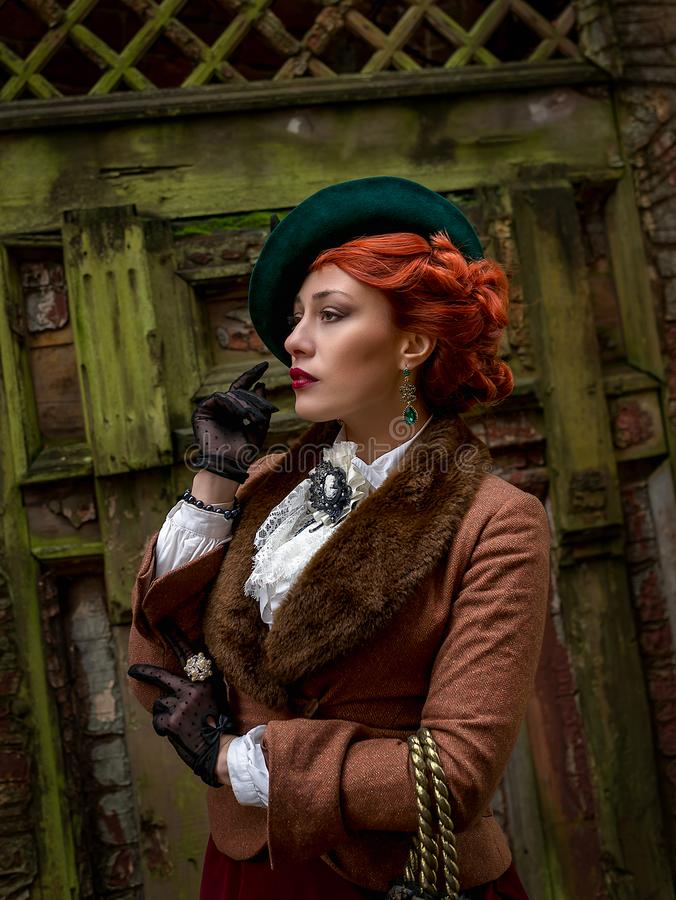 Beautiful woman face in the hat and red hair royalty free stock photography