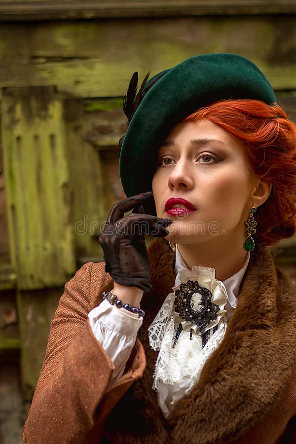 Beautiful woman face in the hat and red hair stock image