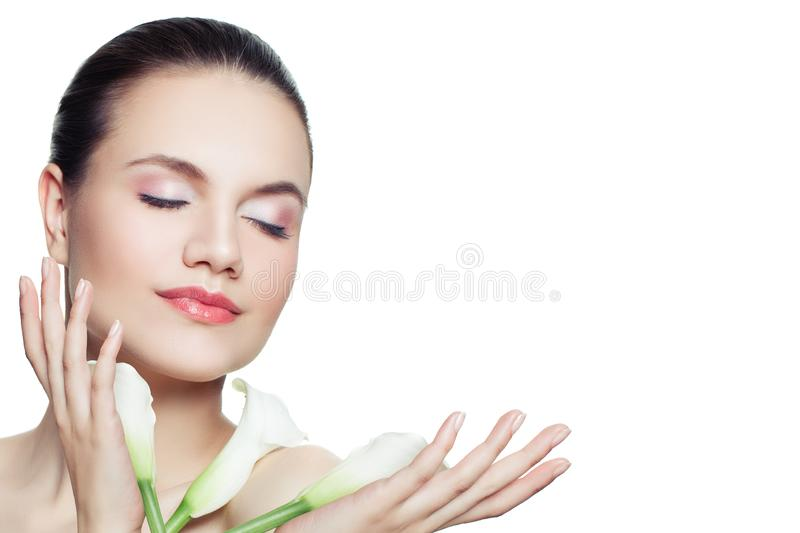 Beautiful woman face. Healthy spa model with clear skin and flowers. Skincare and facial treatment concept royalty free stock images