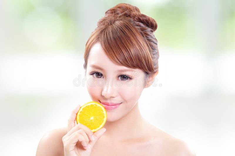 Beautiful woman face with juicy orange