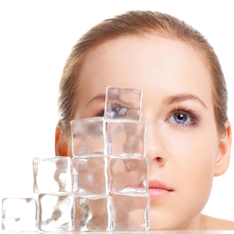 Beautiful woman face near ice cubes. Over white background stock photos