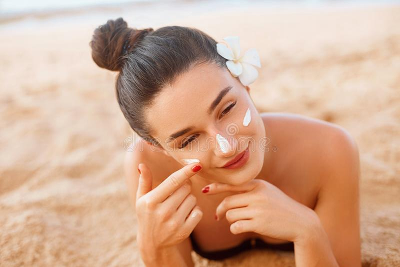 Beautiful Woman Face Portrait Beauty Skin Care Concept. Suncream. Suntan Lotion Beautiful Woman Applying on beautifu on Face. stock photo