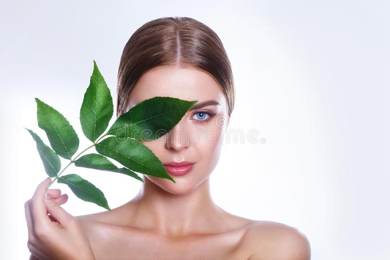 Beautiful woman face portrait with green leaf concept for skin care or organic cosmetics. Studio portrait. Beautiful woman face portrait with green leaf concept royalty free stock photography