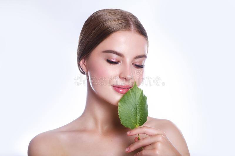 Beautiful woman face portrait with green leaf concept for skin care or organic cosmetics. Studio portrait. Beautiful woman face portrait with green leaf concept stock photos