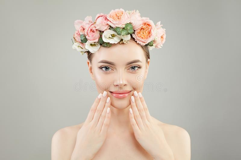 Beautiful woman face. Spa model girl with clear skin, hand with manicured nails and roses flowers on head.  royalty free stock photo