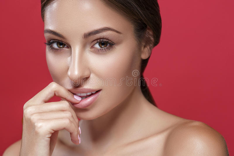 Beautiful woman face touching her lips by fingers close up studio portrait on red. Beautiful woman face close up studio portrait on red background touching her stock image