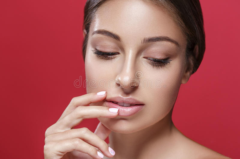 Beautiful woman face touching her lips by fingers close up studio portrait on red. Beautiful woman face close up studio portrait on red background touching her royalty free stock image