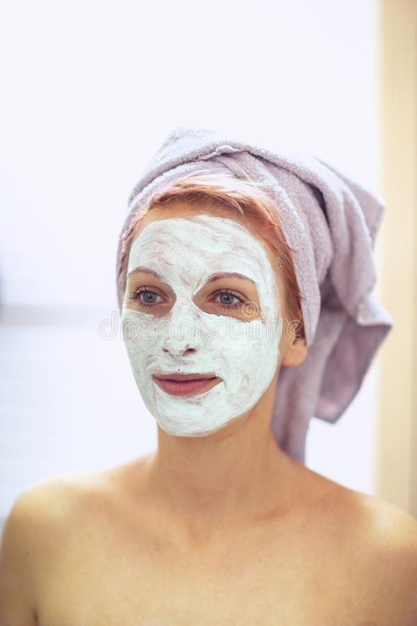 Beautiful woman with facial mask - cream on her face, mask on the face, problem skin stock image