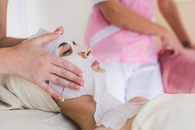 Beautiful woman with facial mask. Female cosmetologist making cosmetic facial mask to the female client at the cosmetology centre stock images