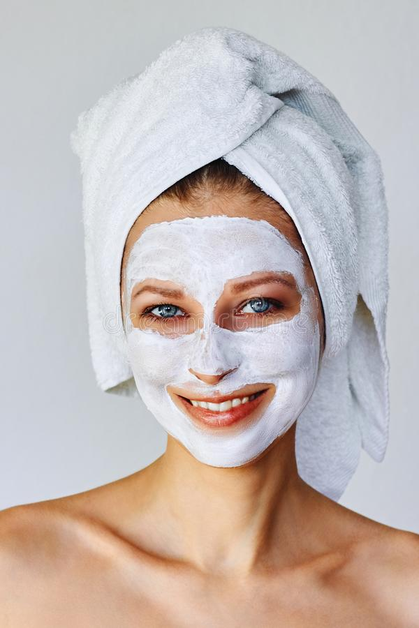 Beautiful woman with facial mask on her face. Skin care and treatment, spa, natural beauty and cosmetology concept stock image