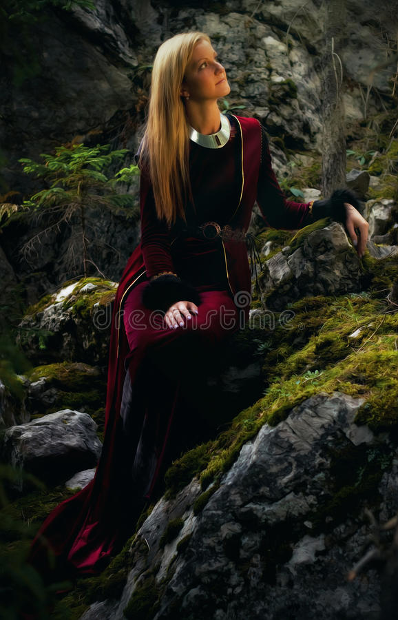 beautiful woman fairy with long blonde hair in a historical gown is sitting amids moos covered rocks stock images