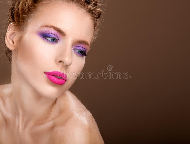 Beautiful woman with fashion bright makeup of eyes and pink. Beautiful woman with fashion bright colorful makeup of eyes and pink lips. Studio shooting over stock photo