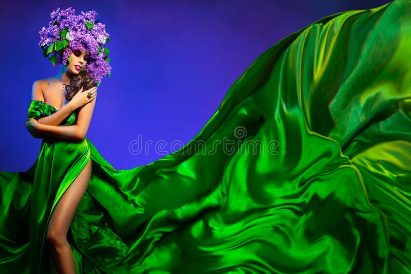 Beautiful Woman in Fashion Flowers Hat and Flowing Green Dress Cloth, Sexy Girl Beauty Art Portrait royalty free stock images