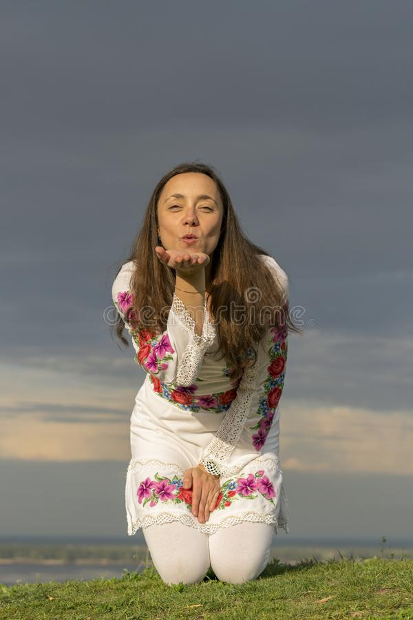 Beautiful woman in fashionable clothes on the background of a dramatic sky. Sexy woman in national clothes. Air kiss. vertical stock photography