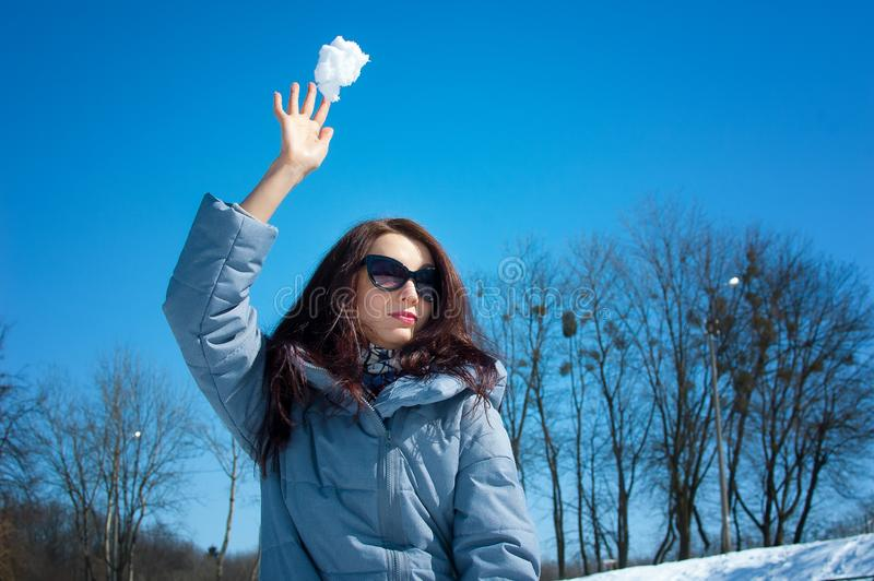 Beautiful woman in fashionable sunglasses and winter clothes throws snow ball playing outdoors on bright sky and bare royalty free stock photography