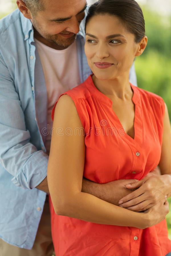 Beautiful woman feeling happy while husband hugging her royalty free stock photo