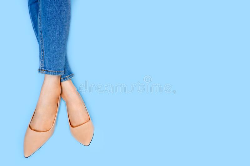 Beautiful Woman Feet & Slim Legs in Beige Medium High Heels on Pastel Blue. Portrait of Legs. Young Female Wearing Jeans stock photography