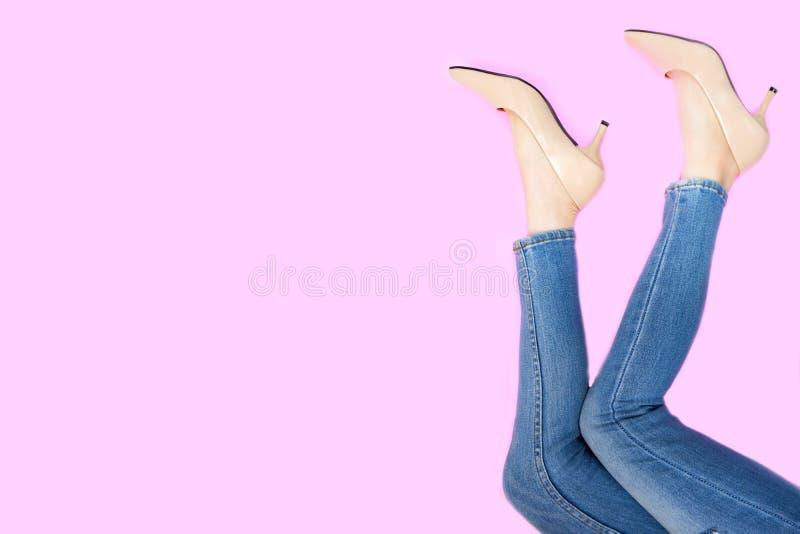 Beautiful Woman Feet & Slim Legs in Beige Medium High Heels on Pastel Pink. Portrait of Legs. Young Female Wearing Jeans stock photos