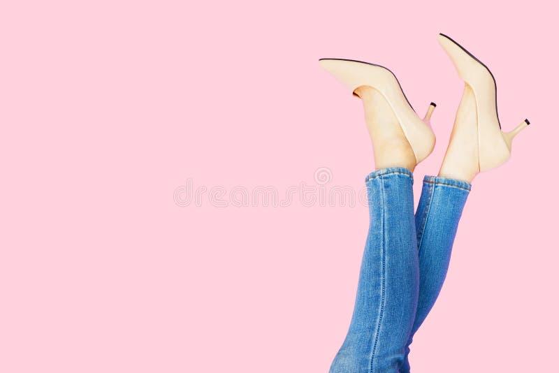 Beautiful Woman Feet & Slim Legs in Beige Medium High Heels on Pastel Pink. Portrait of Legs. Young Female Wearing Jeans royalty free stock photo