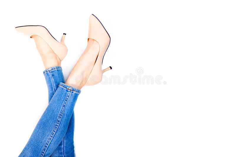 Beautiful Woman Feet and Slim Legs in Beige Medium High Heels. Portrait of Young Women Legs. Young Female Wearing Jeans Blue royalty free stock photos