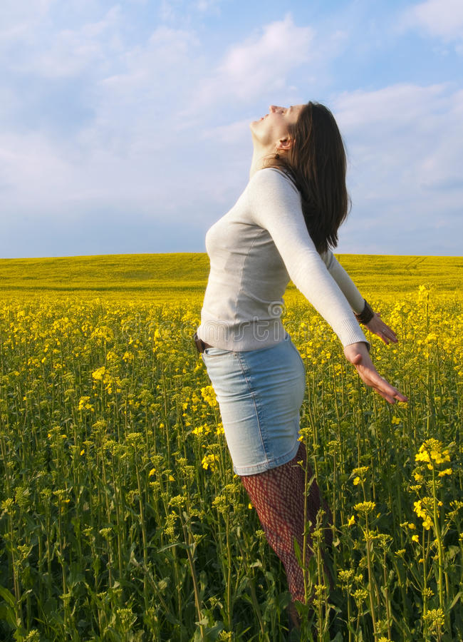 Beautiful woman in field with yellow flowers. royalty free stock photography