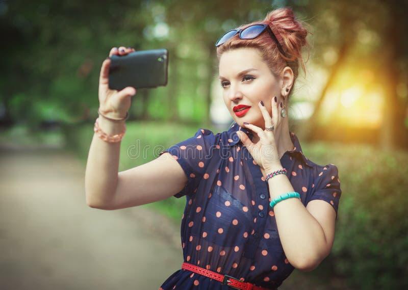 Beautiful woman in fifties style taking picture of herself. Beautiful young woman in fifties style taking picture of herself outdoor stock images