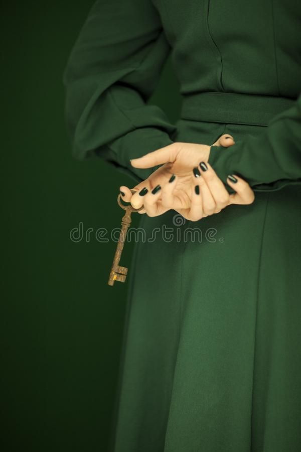 Beautiful woman figure in dark green 50`s dress holding vintage keys royalty free stock photography