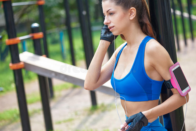 Beautiful woman during fitness on city is listen to the music stock images