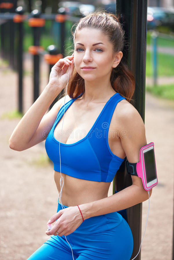 Beautiful woman during fitness on city is listen to the music stock image