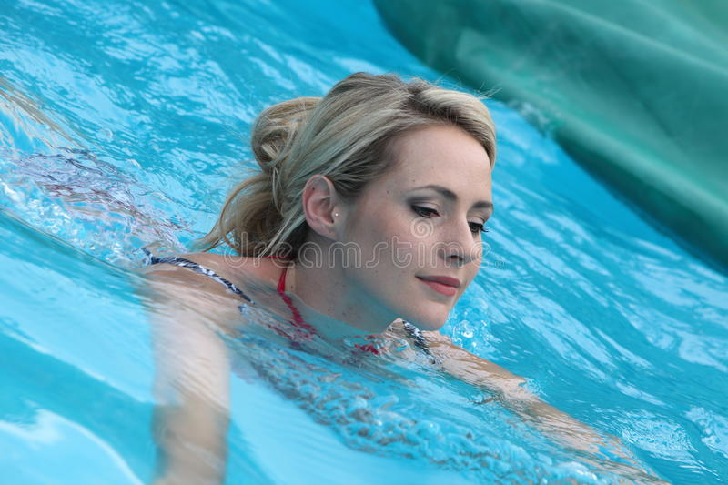 Beautiful woman floating in a swimming pool royalty free stock image