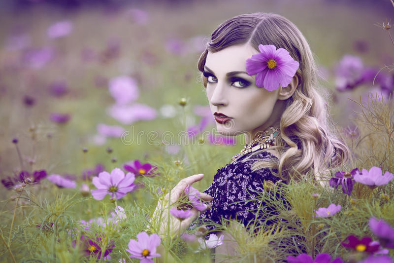 Beautiful woman in flower field stock photography