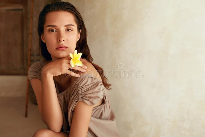 Beautiful Woman With Flower. Portrait Of Tender Model With Tropical Plumeria In Hand. Brunette With Perfect Body. royalty free stock image