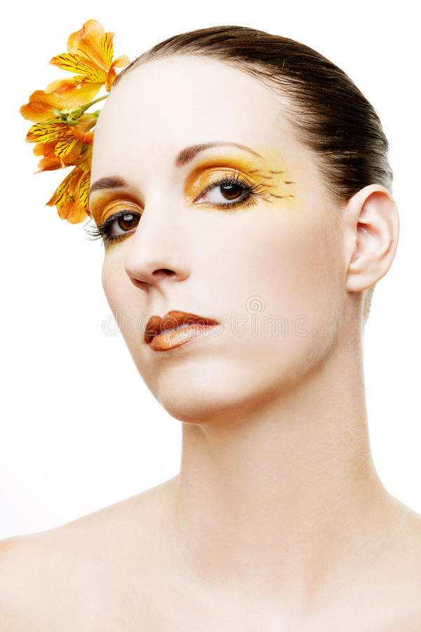 Beautiful woman with flowers in her hair. And colorful orange and yellow make-up royalty free stock images
