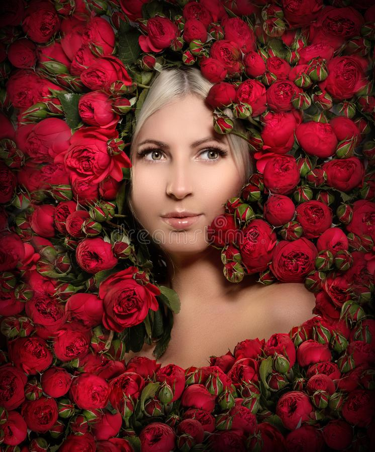 Beautiful woman in a frame of flowers. Young girl with red peony roses stock image
