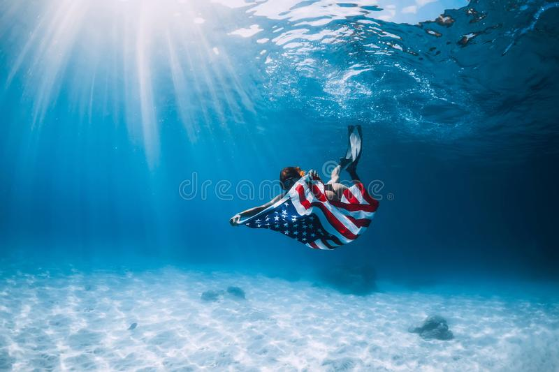Beautiful woman freediver glides over sandy sea bottom with United States flag. Independence day royalty free stock photo