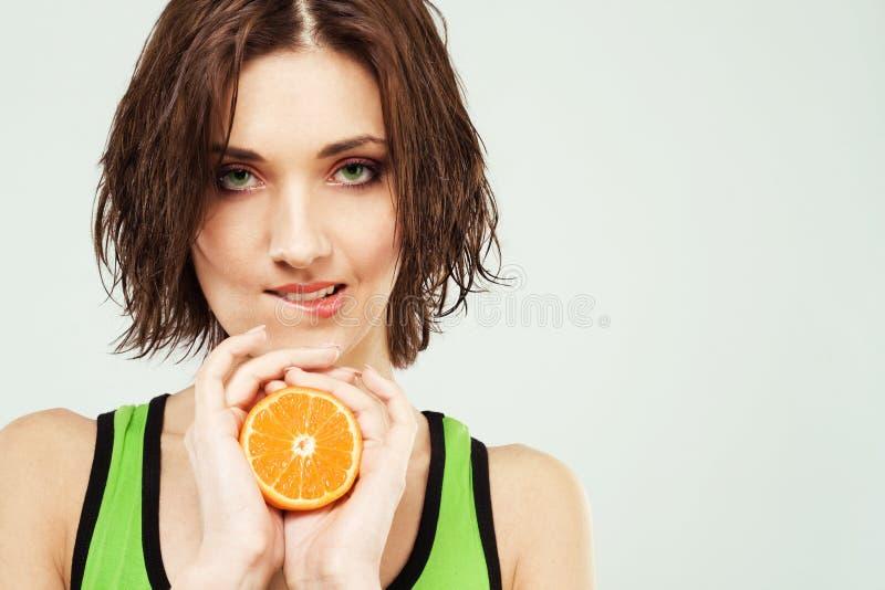 Beautiful woman with fresh orange stock photography