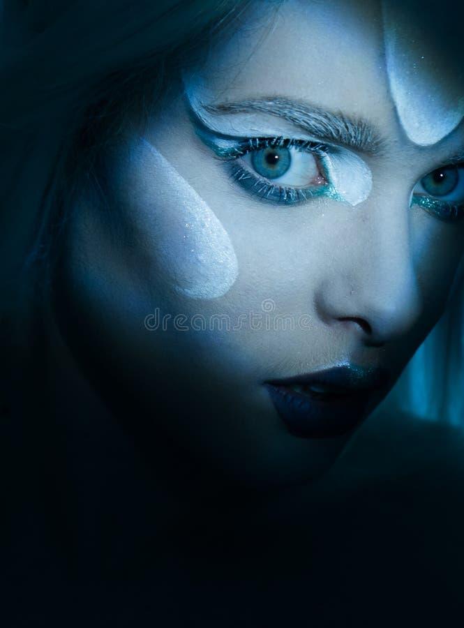 Beautiful Woman with frozen makeup in dark closeup. royalty free stock image