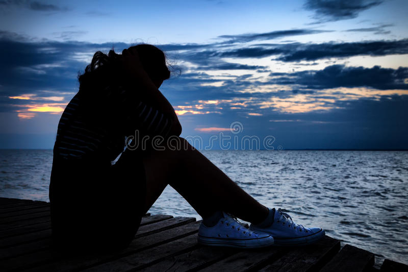 Beautiful woman in frustrated depression sitting on wooden bridge, near the beach on sunset. Concept. Of unemployed, sadness, depressed and human problems in royalty free stock photography