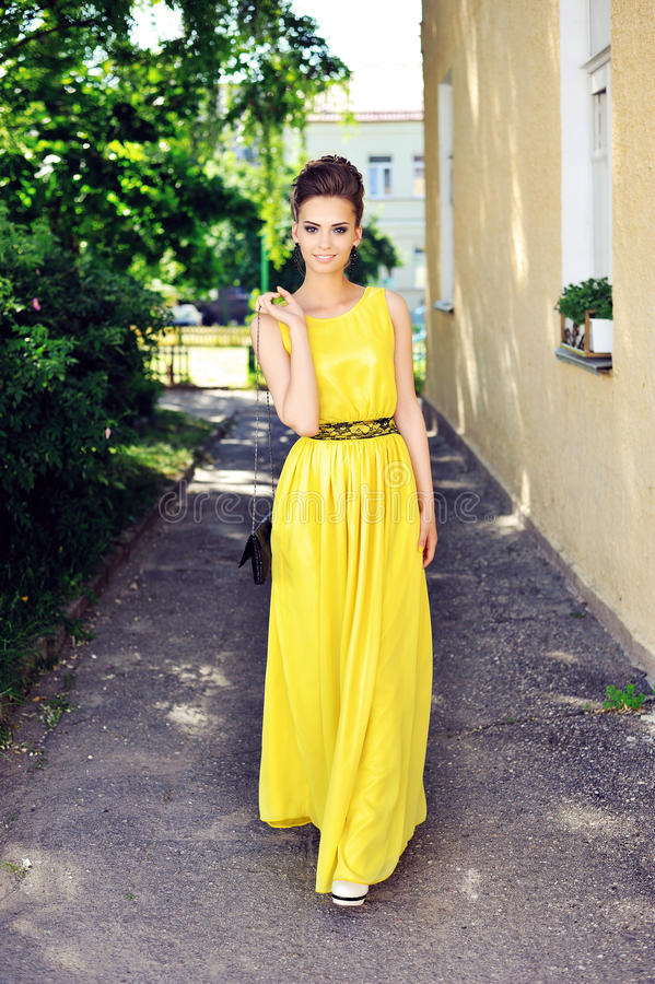 Beautiful woman in full length posing in long yellow party dress.  royalty free stock images